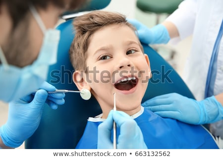 dentists and kid patient at dental clinic Stock photo © dolgachov