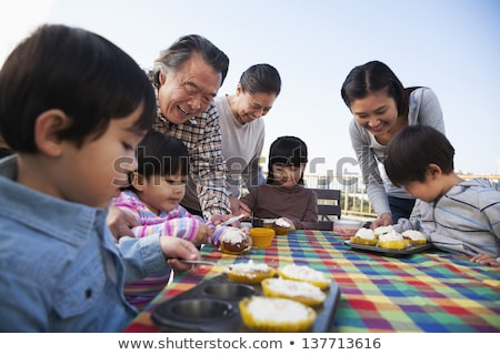 Front view of a multi-generation family celebrating birthday of grandson with a birthday cake at hom Stock photo © wavebreak_media