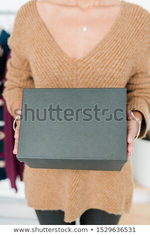 Black box held by young casual shop assistant or customer in beige pullover Stock photo © pressmaster