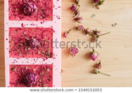 Overview of silicone molds filled with handmade pink soap on wooden table Stock photo © pressmaster