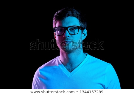 man in glasses over neon lights in dark room Stock photo © dolgachov