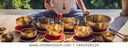 Woman playing on Tibetan singing bowl while sitting on yoga mat against a waterfall. Vintage tonned. Stock photo © galitskaya