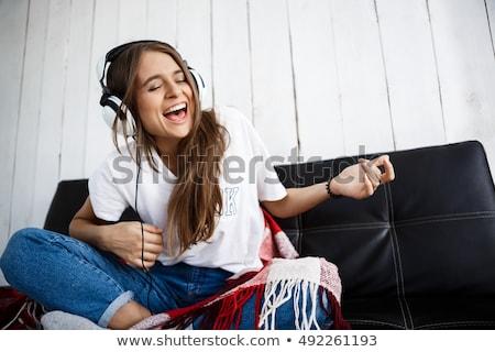 Uśmiechnięty czarnej kobiety sofa słuchanie muzyki piękna młodych Zdjęcia stock © darrinhenry