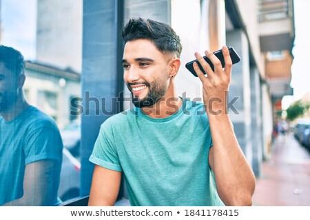 Hombre guapo escuchar voz mensaje sonrisa pelo Foto stock © photography33