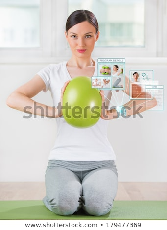 woman doing exercise with ball wearing smart wearable device wit stock photo © hasloo