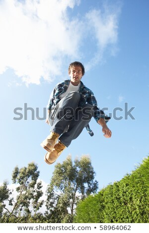 Young Man Jumping On Trampoline Caught In Mid Air Stock photo © monkey_business