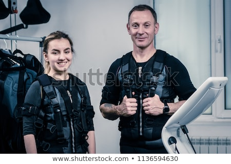 Young woman in training costume near Electro Muscular Stimulation EMS machine  Stock photo © Nejron