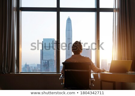 Businesswoman in front of skyscraper window Stock photo © Kzenon