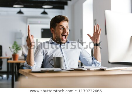 Surprised happy male manager rejoices while using computer Stock photo © deandrobot