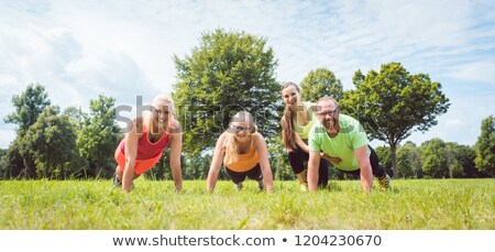 Family doing push-ups in nature under guidance by a fitness coac Stock photo © Kzenon