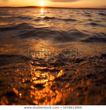 bokeh shot of the sun glittering in the ocean stock photo © kzenon