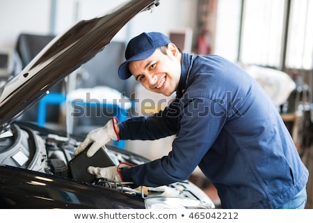 portrait of an auto mechanic putting oil in a car engine stock photo © minervastock