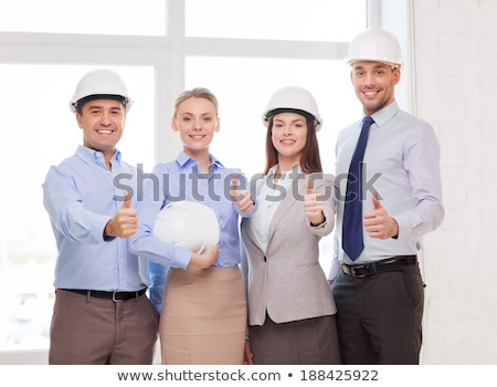 architect in helmet showing thumbs up at office stock photo © dolgachov