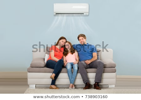 Couple Sitting On Couch Under Air Conditioner Stock photo © AndreyPopov
