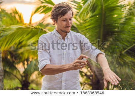 Stock photo: Young man spraying mosquito insect repellent in the forrest, insect protection
