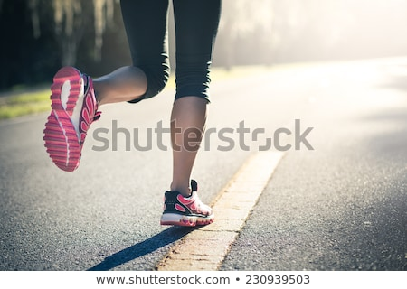Sporty woman running on road at sunrise. Fitness and workout wellness concept Stock photo © galitskaya