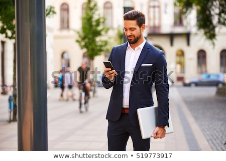 A handsome young businessman holding while using his phone and s stock photo © Freedomz