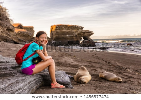 Portrait of woman tourist smiling happy on Galapagos Islands sitting by Sea Lions Stock photo © Maridav