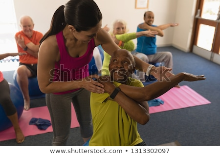 Front view of young female trainer and senior people exercising with resistance band in fitness stud Stock photo © wavebreak_media