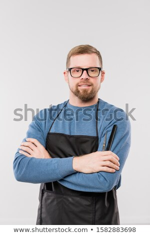 Young bearded hairdresser in apron and blue pullover waiting for clients Stock photo © pressmaster