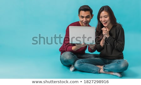 attractive young female sitting on the floor using laptop  stock photo © dacasdo