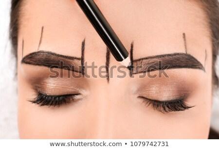 Young woman applying eyebrow pencil Stock photo © get4net