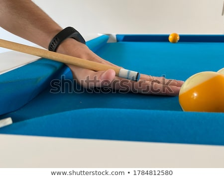 Stock photo: billiard yellow ball player holding cue