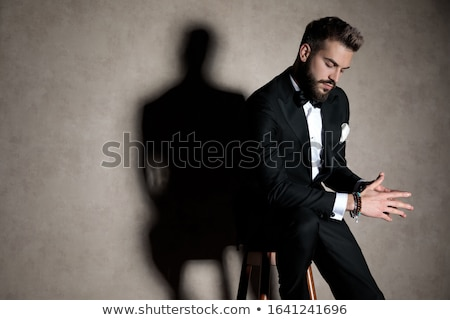 business man sitting on a stool while looking down thinking. Stock photo © feedough