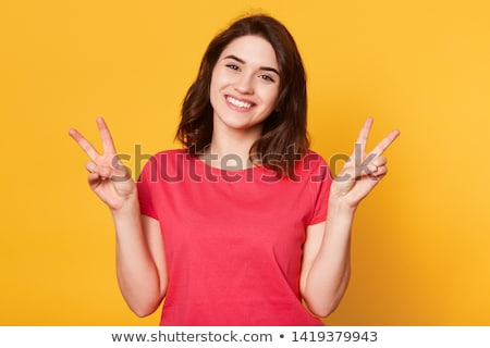 Caucasian woman smiling looking happy showing tshirt on red background Stock photo © deandrobot