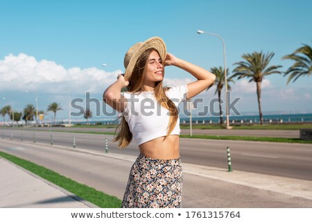 Stock photo: Smiling Blond Woman in front of Palm Trees