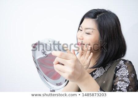 Smiling woman applying tonal cream Stock photo © deandrobot