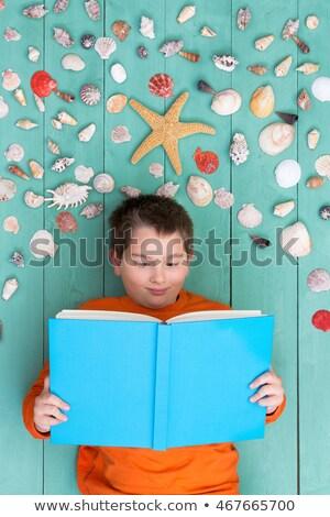Cute мальчика чтение книга ракушки Сток-фото © ozgur