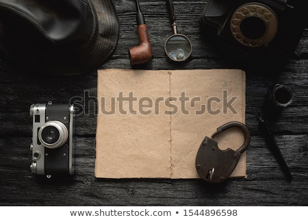 Loupe magnifying glass and notebook on wooden desk, top view Stock photo © stevanovicigor