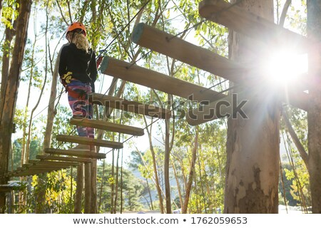 Little girl wearing helmet walking on wooden bridge Stock photo © wavebreak_media