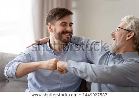 Father and son giving fist bump to each other at home Stock photo © wavebreak_media