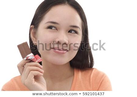 Portré töprengő fiatal nő tart csokoládé szelet izolált Stock fotó © deandrobot