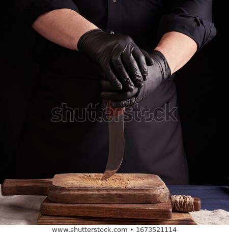 Chef in a apron are standing at the table with wooden cutting board on it on a black background. Stock photo © artjazz
