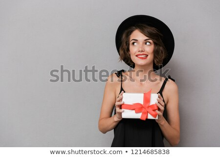 Photo of joyous woman 20s wearing black dress and hat holding gi Stock photo © deandrobot