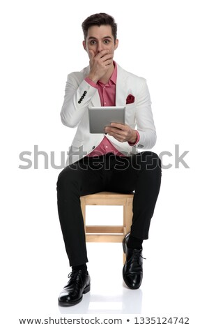 young seated businessman reading amazing news on his tablet Stock photo © feedough