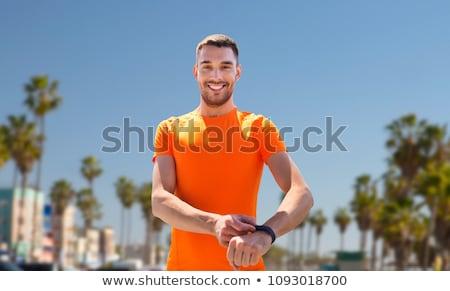 happy man with fitness tracker on summer beach Stock photo © dolgachov