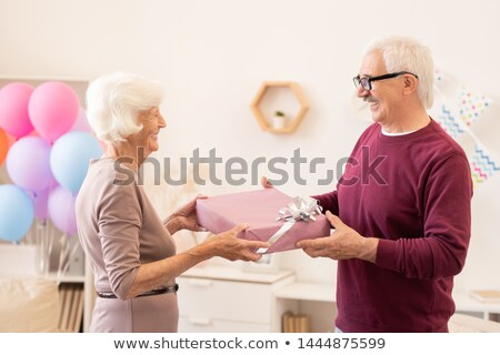 Laughing seniors making presents to one another Stock photo © pressmaster