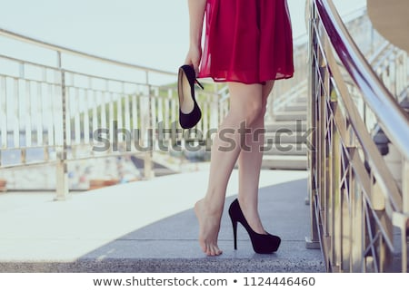 Pretty young business woman stands on the stairs at the office a Stock photo © boggy