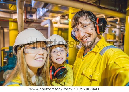 Mom, Dad and Son in a yellow work uniform, glasses, and helmet in an industrial environment, oil Pla Stock photo © galitskaya