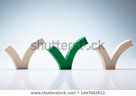 Green Check Mark Between Wooden Check Marks On Desk Stock photo © AndreyPopov