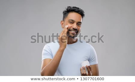 happy indian man applying cream to face Stock photo © dolgachov