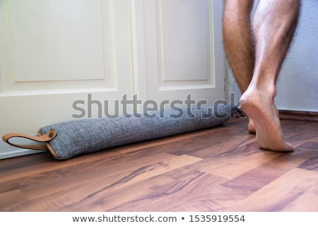 Person Walking Barefoot Near Draft Excluder Under Door Stock photo © AndreyPopov