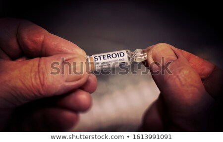 Injection Of Steroid Ampoule In A Wrinkled Hands Foto stock © Tashatuvango