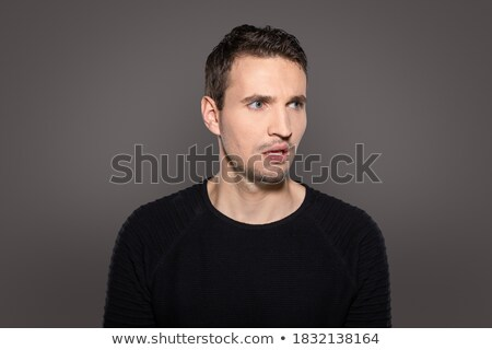Portrait of young indignant man in studio Stock photo © master1305