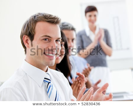 Smiling young business people applauding for presentation in office Stock photo © deandrobot