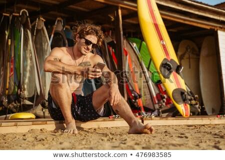 Mosolyog fürtös szörfös férfi fürdőruha ül Stock fotó © deandrobot